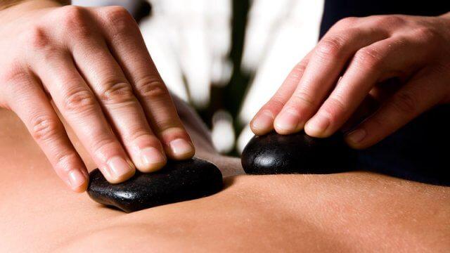 Terpeuta con piedras calientes para masaje